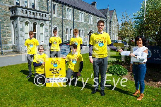 Kacper Bogalecki  presents Marie Carroll the proceeds of the Different clubs same problem club jersey day in aid of Darkness into Light at St Brendans College on Monday with back l-r: James O'Carroll, Tom Knoblauch, Milo Donaldson, Jack Costello and Sam Bolger