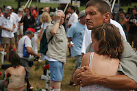 Two participants embrace during a memorial service at Camp Casey in Crawford, Texas.