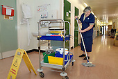 A domestic mops the floor in a ward at Homerton Hospital, Hackney, east London, where threatened industrial action by UNISON members employed by multinational ISS Mediclean in catering, portering and cleaning services lead to a deal which took pay from £4.43 to £5.00 an hour (£5.35 from 1 April 2004),  improved annual leave and the introduction of an occupational sick pay scheme.  The claim was part of the Living Wage campaign carried out in partnership with the East London Citizens Organisation (TELCO).