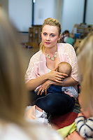 A mother breastfeeds her young baby while talking to other mums at a drop-in breastfeeding support centre.<br /> <br /> Hampshire, England, UK<br /> 12/11/2014<br /> <br /> © Paul Carter / wdiip.co.uk