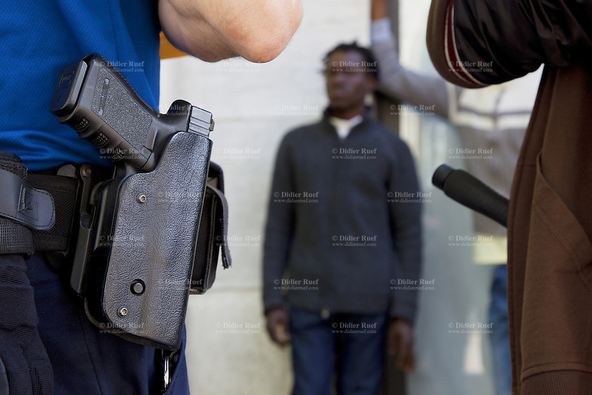 Switzerland. Geneva. Two police officers on duty ( one wears a blue uniform, the other plain clothes) and a convict man. The black man is arrested while selling drugs in the streets. The inmate is an african man from Guinea. The policeman carries a holster with a Glock hand gun. The weapon is a semi-automatic pistol designed and produced by Glock Ges.m.b.H. Glock was the first manufacturer to introduce ferritic nitrocarburizing into the firearms industry as an anti-corrosion surface treatment for metal gun parts. 3.05.12 © 2012 Didier Ruef..