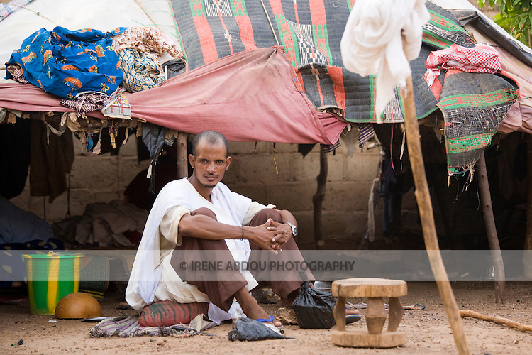 A Touareg man sits in front of his tent in Ouagadougou, Burkina Faso.  The Touareg are traditionally nomadic, traversing the deserts of Mauritania, Mali, Niger, Chad, Libya, and Algeria. Traditionally, the roof of the tent would be pieced together from leather animal hides, but this family in Ouagadougou has made a roof of more modern materials.