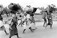 """Mozambique. Province of Gaza. Chokwe. The Limpopo river has flooded in february the whole town."""" Local authorities, fearing a new flood, order the population to leave the town. Families flee with their belongings. The women carry the children on their backs. © 2000 Didier Ruef"""