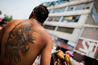 A Mexican follower of Santa Muerte (Saint Death) shows his tattoo during a religious procession in Tepito, a rough neighborhood of Mexico City, Mexico, 1 May 2011. The religious cult of Santa Muerte is a syncretic fusion of Aztec death worship rituals and Catholic beliefs. Born in lower-class neighborhoods of Mexico City, it has always been closely associated with crime. In the past decades, original Santa Muerte's followers (such as prostitutes, pickpockets and street drug traffickers) have merged with thousands of ordinary Mexican Catholics. The Saint Death veneration, offering a spiritual way out of hardship in the modern society, has rapidly expanded. Although the Catholic Church considers the Santa Muerte's followers as devil worshippers, on the first day of every month, crowds of believers in Saint Death fill the streets of Tepito. Holding skeletal figurines of Holy Death clothed in a long robe, they pray for power healing, protection and favors and make petitions to 'La Santísima Muerte', who reputedly can make life-saving miracles.