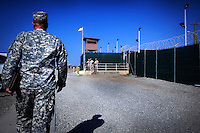 A guard walks towards the entrance of Camp Delta at the American naval base at Guantanamo Bay, where over 600 alleged al Qaeda members have been held indefinitely. Described by the US as 'unlawful enemy combatants', they were captured primarily in Afghanistan during the 'war against terror'.