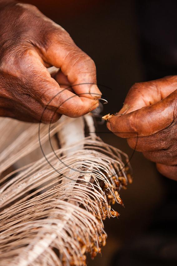 Africa, Ghana,preparing bait for fishing with fishhooks
