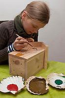 Nistkasten, Mädchen, Kind bemalt selbstgebauten Vogel-Nistkasten