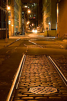 THIS IMAGE IS AVAILABLE EXCLUSIVELY FROM CORBIS.....PLEASE SEARCH FOR IMAGE # 42-20075389 ON WWW.CORBIS.COM....Mysterious Street Scene at Night, with remains of old train tracks and cobblestone street, Brooklyn Bridge in the background, the DUMBO neighborhood of Brooklyn, New York City, New York State, USA