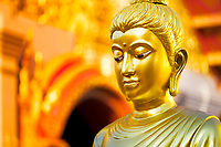 Famous Wat Phra That temple, golden Buddha with blurred, gold chedi background in Doi Suthep mountains near Chiang Mai Thailand, Southeast Asia