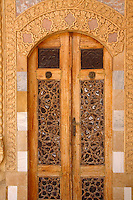 An pair of carved wooden doors inset with mosaic and outlined with traditional motifs