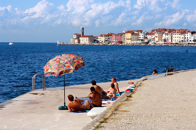 Friends with their umberella sunbathing and talking. Piran , Slovenia