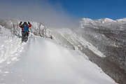 A winter hiker, wearing snowshoes, breaks trail while ascending the Old Bridle Path in the White Mountains of New Hampshire during the winter months.