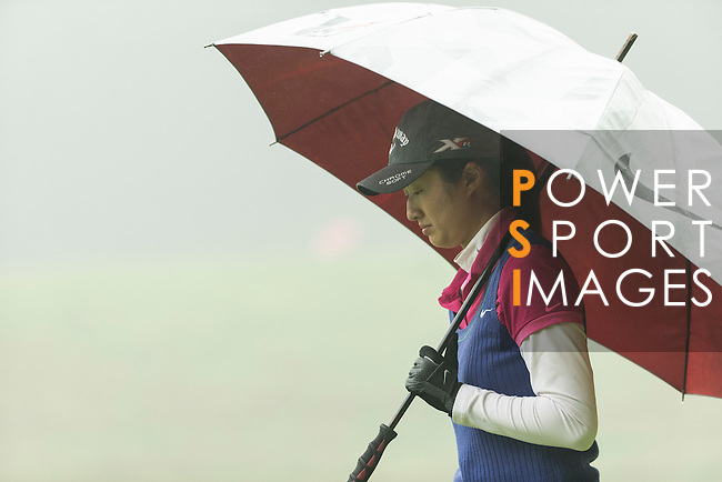 Liu Yu of China protects herself from the rain at the 13th hole during Round 4 of the World Ladies Championship 2016 on 13 March 2016 at Mission Hills Olazabal Golf Course in Dongguan, China. Photo by Victor Fraile / Power Sport Images