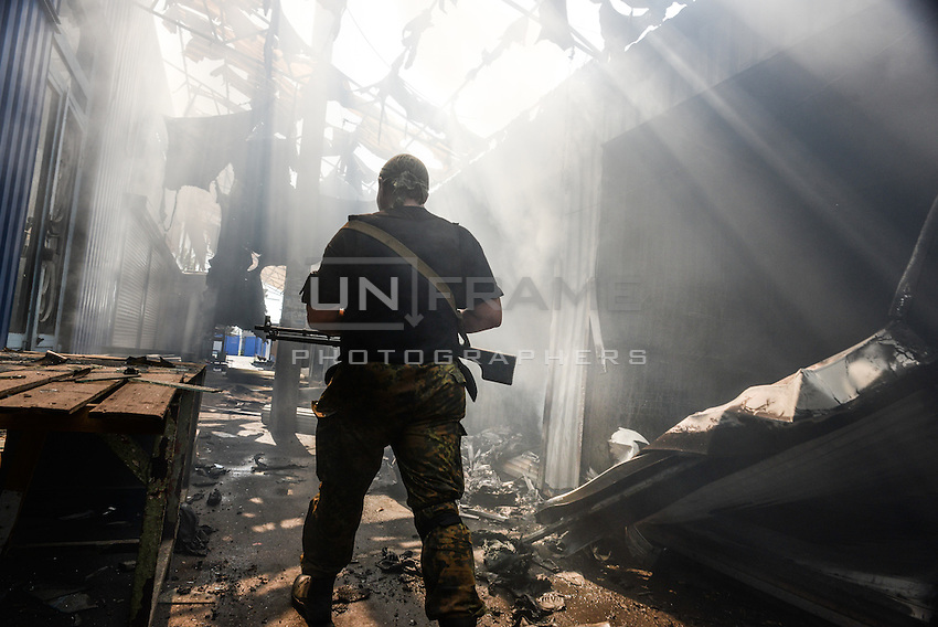 Pro-Russian rebel walks by line of shops burned and destroyed by shelling. Donetsk, Eastern Ukraine