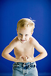 young boy shows off his strength by posing with his shirt off like in a strong man contest against a blue background