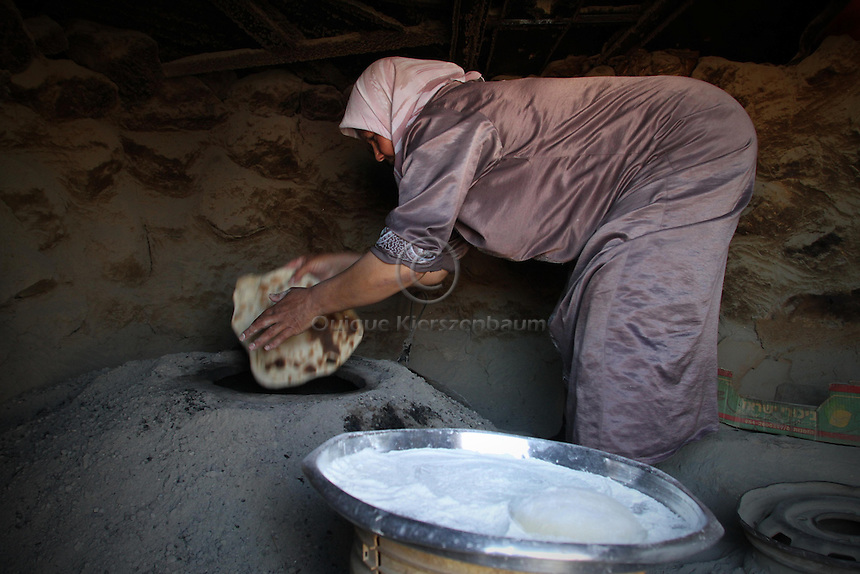 """A woman bakes bread in Jenba a Palestinian town of 50 families seats in an area called by the IDF as """"Firing Zone 918"""" and is located in the southern Hebron hills near the town of Yatta.  Spread over 30,000 dunams, it includes twelve Palestinian villages.  According to OCHA figures, 1,622 people lived in the area in 2010, and according to local residents the number of inhabitants currently stands at about 1,800. For over a decade, the residents of twelve uniquely traditional Palestinian villages in the area of Masafer-Yatta in the south Hebron hills have lived under the constant threat of demolition, evacuation, and dispossession.<br /> <br /> The State's insistence on evacuation of Firing Zone 918 in part or in whole, if acceptance by the HCJ, might result in an immediate humanitarian disaster for almost two thousand souls, the destruction of villages, and the eradication of a remarkable way of life that has endured for centuries."""