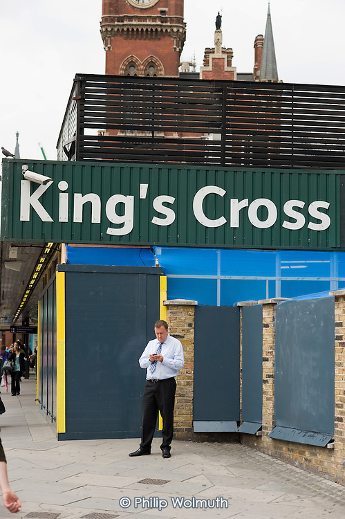 A man uses a mobile phone outside King's Cross station, London