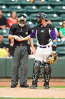 Home plate umpire Junior Valentine hands a new baseball to Winston-Salem Dash catcher Martin Medina (22) during the Carolina League game against the Frederick Keys at BB&T Ballpark on July 21, 2013 in Winston-Salem, North Carolina.  The Dash defeated the Keys 3-2.  (Brian Westerholt/Four Seam Images)