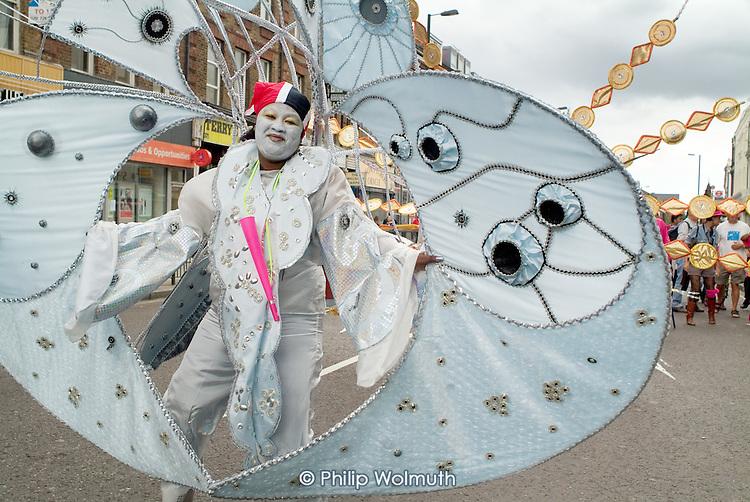 Members of Flamboyan Carnival Arts parade in costume at Notting Hill Carnival, London