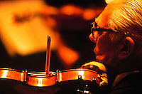 Detail view in warm lighting of an Oregon Symphony Orchestra violinist performing during a rehersal.