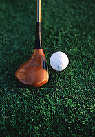 Close up of a golf ball and driver.