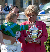 Jimmy Moran plays with the trophy named in memory of his grandfather, James Moran. That's Jimmy's mother, Megan, and great grandmother, Betty. alongside. Little Jimmy is wearing the colors of Betty's fabled Brushwood Stable.