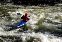 Blurred motion image of a kayaker in action in the rough waters of the Deschutes River. Bend, Oregon.