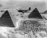 An Air Transport Command plane flies over the pyramids in Egypt.  Loaded with urgent war supplies and materials, this plane is one of a fleet flying shipments from the U.S. across the Atlantic and the continent of Africa to strategic battle zones.  1943. (Army)<br /> Exact Date Shot Unknown<br /> NARA FILE #:  111-SC-179564<br /> WAR & CONFLICT BOOK #:  1015