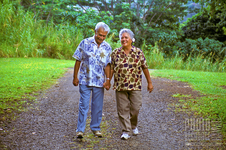 Affectionate senior Hawaiian man and part-Hawaiian woman walking along a park path and holding hands; Hoomaluhia Botanical Gardens, Kaneohe, Windward Oahu