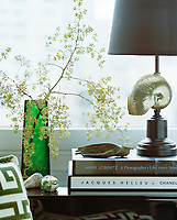 Nature and natural tones are celebrated in every corner. Here, a green glass vase plays host to a blossom spring, while seashells are celebrates in their natural and artistic forms.
