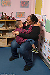 Education preschool childcare 3-4 year olds boy sitting on female teacher's lap interacting with her