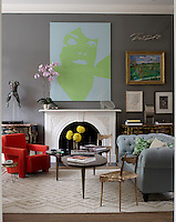 A pair of gilded commodes flanks the marble fireplace in the living room which is filled with a collection of antiques and contemporary works of art