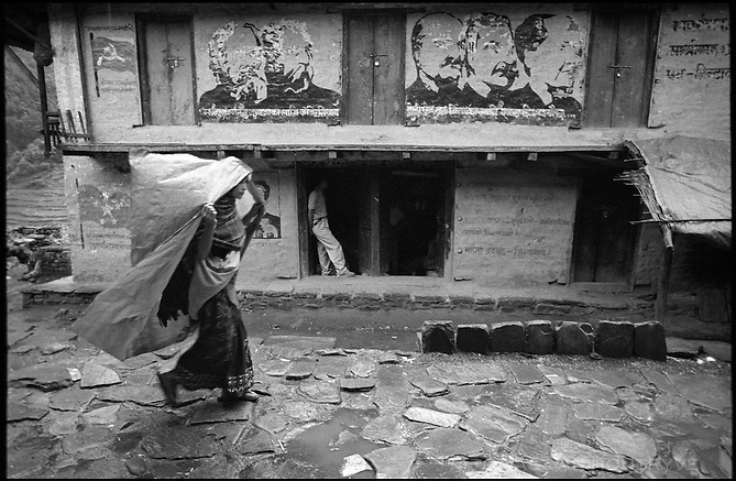 A village woman covered in plastic to escape the rain wlaks past a mural of Marx, Engels, Lenin, Stalin and Mao in Thabang, the capital of Nepal's Maoist held areas on 20 June 2005. The rebels have decorated the entire town with communist symbols, flags and images of revolutionaries. Royal Nepal Army troops defaced the images during a previous raid on the village.<br />