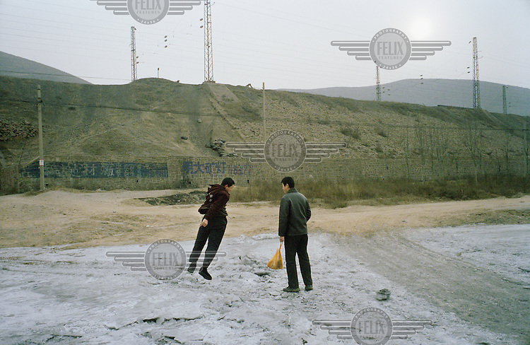 16 year old Lao Liu larks about with a friend on a day off from their jobs in a coal mine.