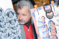 James Bragg, of Dallas, Tex., sells buttons, shirts, hats, and other Cruz merchandise made by My Campaign Wear, while Texas senator and Republican presidential candidate Ted Cruz speaks at a town hall at The Alpine Grove banquet center in Hollis, New Hampshire.