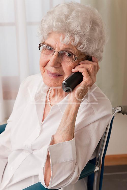 USA, Illinois, Metamora, Portrait of smiling senior woman on wheelchair talking on phone