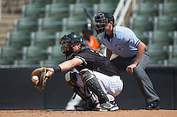 Kannapolis Intimidators catcher Nate Nolan (24) catches a pitch as home plate umpire Anthony Perez looks on during the game against the Greensboro Grasshoppers at Intimidators Stadium on July 17, 2016 in Greensboro, North Carolina.  The Intimidators defeated the Grasshoppers 3-2 in game one of a double-header.  (Brian Westerholt/Four Seam Images)