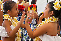 Two young hula dancers playing a hand game at the 2011 Kauai Polynesian Festival