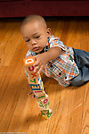 21 month old toddler boy sitting on floor playing with alphabet blocks stacking them into tower