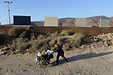 Several border wall prototypes being built in San Diego, 10/12/17, near the Mexican border are seen from Mexico on the north side of the existing wall as a woman walks by pushing some of her belongings.