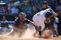 Omar Carrizales (19) of the Asheville Tourists slides across home plate ahead of the tag by Tanner Murphy (14) of the Rome Braves as home plate umpire Kyle Wallace looks on at McCormick Field on July 26, 2015 in Asheville, North Carolina.  The Tourists defeated the Braves 16-4.  (Brian Westerholt/Four Seam Images)