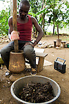 Man mashing up vegetable peels and paper to create bricks to be used for fires instead of illegaly cut wood from protected area, Kibale National Park, western Uganda