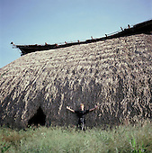 Pavuru Indian village, Brazil. Sting standing outside a large oca; Xingu Indigenous area; Nov 1990.