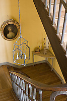 The staircase landing is furnished with a corner table and an oval gilt-framed portrait