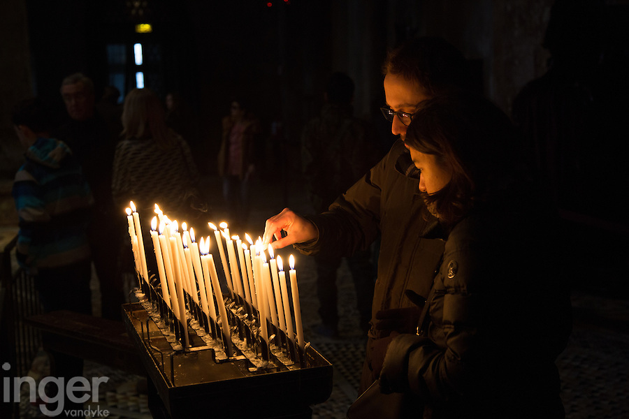 People lighting candles inside Saint Mark's Basilica in Venice, Italy