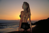Beautiful young blond woman on tropical island's sunset
