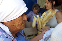 "An old woman waits in the line to receive basic food at ""Caras Sucias"", an institution that gives food to poor people in Buenos Aires, January 19,2002. Volunteers directed by Monica Carransa gather food and other basic elements and give them to poor people in the poor neighborhood of Matanza. Photo by Quique Kierszenbaum.."