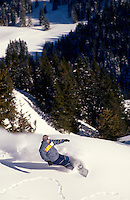 A snowboarde running downhill.