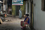 A sex worker sits in front of her door all deced up for customers at Sonagach in Kolkata. Sonagachi is the biggest red light area in Asia. She did not find any customer for few days as India is going through a 21 days lock down due to covid 19 pandemic. Kolkata, West Bengal, India. Arindam Mukherjee.