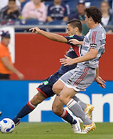 Clint Dempsey (Revolution, blue) crosses the ball as Kenny Cooper (Dallas, gray) defends. The New England Revolution defeat FC Dallas, 1-0, on June 28 at Gillette Stadium.